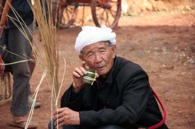 De sjamaan Loiseng Gam met zijn ceremoniele strobundel, drinkend uit ceremoniele bamboe beker.